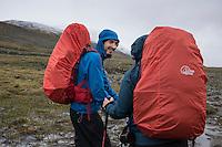 Two hikers on rainy day near Tjäktja hut, Kungsleden trail, Lapland, Sweden