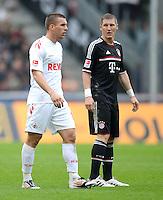 FUSSBALL   1. BUNDESLIGA  SAISON 2011/2012   34. Spieltag 1. FC Koeln - FC Bayern Muenchen        05.05.2012 Lukas Podolski (li, 1. FC Koeln) mit Bastian Schweinsteiger (FC Bayern Muenchen)