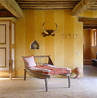 An antique daybed is situated beneath a hunting trophy hanging on a wall painted in yellow and gold stripes