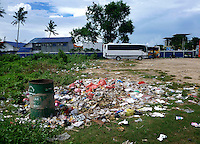 Trash litter a parking lot used by tour buses catering to tourists visiting the beach at Tanjung Benoa, South Bali.