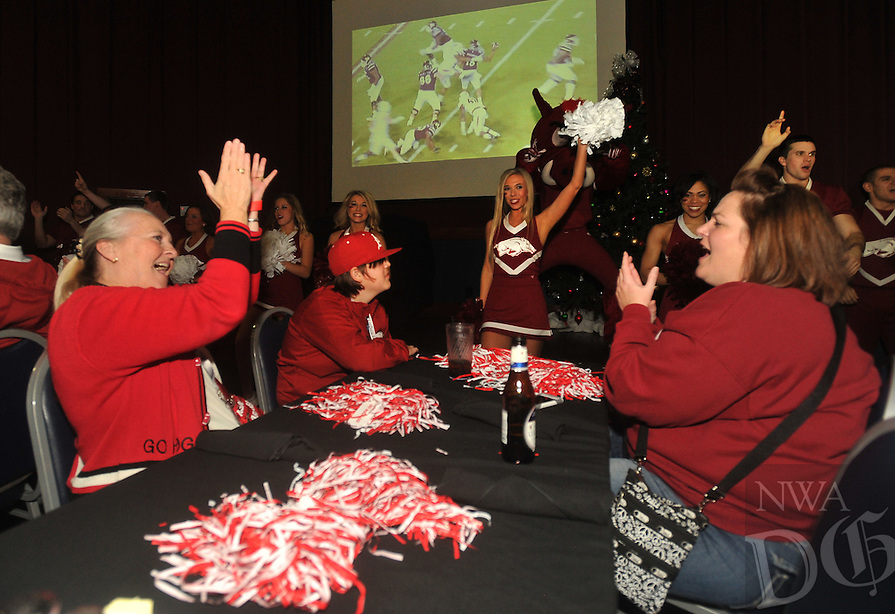 NWA Media/Michael Woods --12/28/2014-- w @NWAMICHAELW...Evelyn Smith (left) and Tonya Green, from North Little Rock call the hogs Sunday night during a pep rally at <br /> Dave and Busters in Houston.  The Razorbacks take on the Texas Longhorns in the Texas Bowl Monday night.