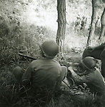 United States Army soldiers of the Second Infantry Division man a 30 caliber machine gun as soldiers in the back ground assess the situation during the summer or early fall of 1951. These are photos of the Second Infantry Division, one of the first units to arrive and fight against North Korea and China during the Korean War along side the South Koreans and other troops from the United Nations.
