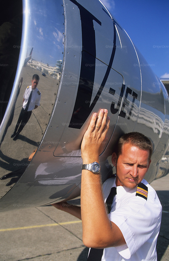 "Crew of John Travolta's jumbo jet. Stewards on runway, reflected against  fuselage of aircraft...John Travolta is pilot of his very own jumbo jet, a 1964 Boeing 707-100 series. In 2003, John Travolta flew his jumbo jet around the world, in partnership with Quantas, to rekindle confidence in commercial aviation, and to remind us that elegance and style are a part of flying. The crew are dressed in tailor made authentic uniforms from the Quantas museum. The men's uniforms are styled on British Naval uniforms and the ladies' designed by Chanel. His jumbo jet sports a personalised number plate N707JT which speaks for itself. The aircraft is named ""Jett Clipper Ella"" dedicated to his son and daughter. This jumbo together with his other aircraft are housed in purpose built hangars at his home in Florida, USA."