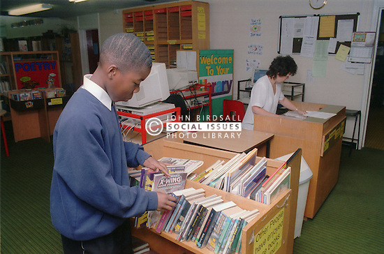 Secondary school pupil choosing book in library,