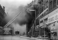 Firemen fight blaze at The Athletic Stores Ltd caused by a Provisional IRA fire bomb, 23rd January 1974. The late Victorian building was a Belfast, N Ireland landmark. 197401230037a. <br />