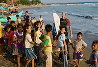 Surfer and children, S. Sumatra, Indonesia