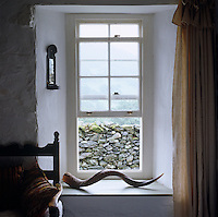 A curved horn on the sill before an open sash window