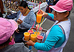Women with colorful drinks in Otavalo marketplace in Ecuador