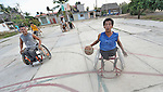 Bartolome Martinez dribbles the basketball while pushing his wheelchair forward during practice in Zipolite, a town in Oaxaca, Mexico. Martinez and the other players are part of the Oaxaca Costa wheelchair basketball team.