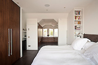 Warm wooden floors and built-in wardrobes soften an all-white colour scheme in this contemporary London bedroom