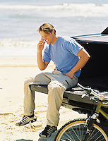 Man at the beach sitting on the back of a truck while talking on a cell phone