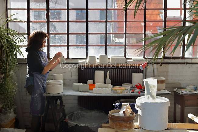 Ceramicist Valeria Polsinelli at work on a vase by the window, photographed in 2017, in her studio in Montreuil, a suburb of Paris, France. Polsinelli creates everyday vessels, water jugs, jewellery and figurines and stoppers of female busts, with features and hairstyles from various world cultures. Picture by Manuel Cohen