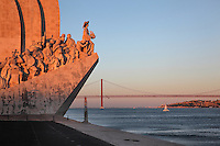Padrao dos Descobrimentos or Monument to the Discoveries, and the 25 de Abril suspension bridge crossing the Tagus river estuary, Santa Maria de Belem, Lisbon, Portugal. The monument was built 1958-60, replacing an earlier monument built for the 1940 Portuguese World Fair, to celebrate the golden age of Portuguese exploration. The monument opened on the 5th centennial of the death of Henry the Navigator and features 33 statues of figures from the exploration age led by Henry the Navigator holding a model carrack. Picture by Manuel Cohen