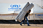 A man carries mattresses in the Zaatari Refugee Camp, located near Mafraq, Jordan. Opened in July, 2012, the camp holds upwards of 50,000 refugees from the civil war inside Syria. International Orthodox Christian Charities and other members of the ACT Alliance are active in the camp providing essential items and services.