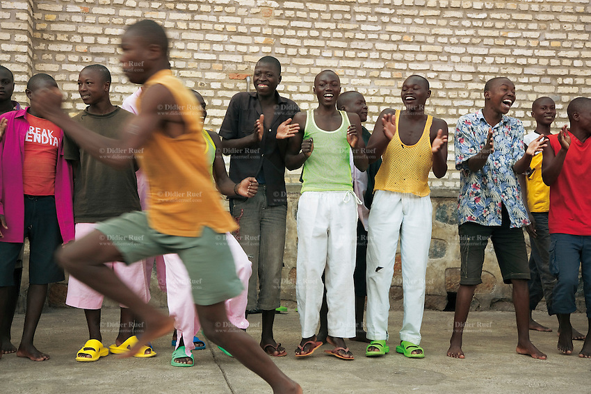 Rwanda. Southern province. District of Muhanga. Central jail of Gitarama. A group od young black boys shouts, roars and engourages the runners during a race on the concrete playground. Bricks wall. Minors block. Minors in detention. Detention pending trial and after trial, when sentenced to prison. The non-governmental organization (NGO) Fondation DiDé - Dignité en détention runs the Encademi (Encadrement des mineurs) program. Prison centrale de Gitarama. Quartier des mineurs.  © 2007 Didier Ruef