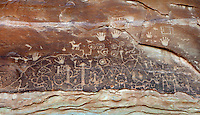 Petroglyphs, pictures etched into the rock surface, depicting ancestral Puebloans along the bottom, with other clans at the top including (left-right) Mountain Lion clan, Horned Toad clan, Parrot clan, Mountain Sheep clan and Eagle clan, on the Petroglyph Point Trail, Mesa Verde National Park, Montezuma County, Colorado, USA. The double spiral is a sipapu, representing the place where Pueblo people believe they emerged from the earth, so the rock face tells the story of various clans, their origins and movements. Mesa Verde is the largest archaeological site in America, with Native Americans inhabiting the area from 7500 BC to 13th century AD. It is listed as a UNESCO World Heritage Site. Picture by Manuel Cohen