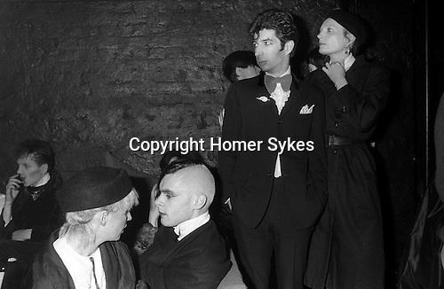 New Romantics, Heaven nightclub Villiers Street, Charing Cross, London, 1980.   Duggie Fields in centre wearing bow tie. The actress Jenny Runacre standing next to DF. John Crancher fashion designer seated, with a combed Mohawk hairstyle.