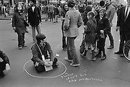 "22 Apr 1970 --- Pedestrians walk past a demonstrator who is sitting in the middle of the street inside a chalk circle with the message ""Please don't hit the pedestrian"" pointing at him. Various public demonstrations and rallies are taking place around New York City during the first Earth Day. --- Image by © JP Laffont/Sygma/CORBIS"