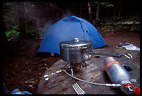 A STAINLESS STEEL COOKPOT SIMMERS ON A ONE-BURNER STOVE WITH A TENT IN THE BACKGROUND ON ISLE ROYALE NATIONAL PARK.