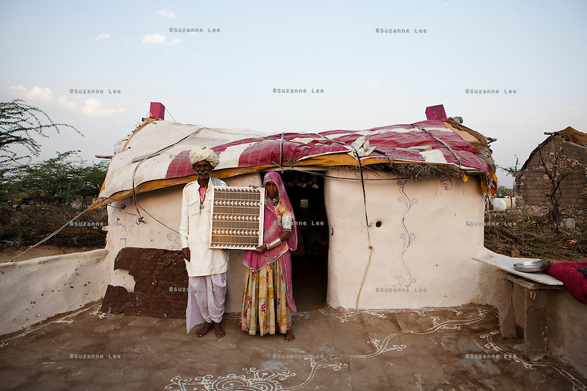 Nomads Kanaram Banjara, aged 55, and his wife Manju Banjara, aged 50, pose for a portrait with their solar panel in front of their mud hut in Banjara Ki Dhani. Ancestrally known as rich salt merchants, until commercially packaged salt was available in the market, they now work as daily wage labourers in nearby agricultural fields. Three years ago, the Barefoot College in Tilonia, Ajmer, Rajasthan, India, had come to sell solar panels and lanterns to them at INR 1000 per set. Photo by Suzanne Lee for Panos London