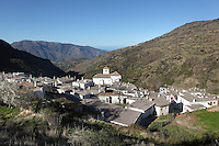 Bubion, rooftop view with mudejar style Church of La Virgen del Rosari, 16th century, gorge of the Poqueira river, Alpujarra, Andalucia, Southern Spain. Moorish influence is seen in the distinctive cubic architecture of the Sierra Nevada's Alpujarra region, reminiscent of Berber architecture in Morocco's Atlas Mountains. Photograph by Manuel Cohen.