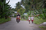 "Two boys walk to school in Tugala, a village on the Indonesian island of Nias. The village was struck by both a 2004 tsunami and a 2005 earthquake, leaving houses destroyed and lives disrupted. The ACT Alliance helped villagers here to construct new homes and latrines, build a potable water system, open a clinic and schools and get their lives going once again. For the residents of Tugala, the post-disaster mantra of ""build back better"" became a reality with help from the ACT Alliance."