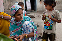 Nafeesa (center, in blue), 27, rolls bidis (indian cigarettes) with other village women as her children play in her house compound in a slum in Tonk, Rajasthan, India, on 19th June 2012. Nafeesa's health deteriorated from bad birth spacing and over-working. While her husband works far from home, she rolls bidis to make an income and support the family. She single-handedly runs the household and this has taken a toll on her health and financial insufficiencies has affected her children's health. Photo by Suzanne Lee for Save The Children UK