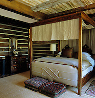 A contemporary upholstered four-poster bed with a carved headboard dominates the bedroom