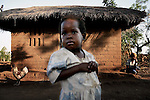 GALUFU, MALAWI NOVEMBER 11: Ndaona, age 4, (c), stands outside the family house with her grandmother Millenia Masaza, age 73, (r) on November 11, 2005 in Galufu, Malawi. Ndaona lost her mother Hilda Rafael, age 32, a month earlier to HIV/Aids. The young woman left Ndaona and her younger brother Limbani aged 7 months. The grandmother now has to take care of the orphans without any income. The village has seen an increase in poverty the last few years due to drought and HIV/Aids. Southern Africa has been hit by a severe hunger crisis due to drought and poverty and government policies. An ever-increasing HIV/Aids rate adds to the misery. Malawi is one of the worst hit areas and Galufu village is a typical small village that has become victim of this poverty spiral. (Photo by Per-Anders Pettersson)