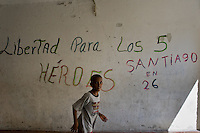 A Cuban boy runs in front of a propaganda writing (?Five Heroes?) painted on the wall in Abel Santamaría, the social housing neighbourhood of Santiago de Cuba, Cuba, 31 July 2008. About 50 years after the national rebellion, led by Fidel Castro, and adopting the communist ideology shortly after the victory, the Caribbean island of Cuba is the only country in Americas having the communist political system. Although the Cuban state-controlled economy has never been developed enough to allow Cubans living in social conditions similar to the US or to Europe, mostly middle-age and older Cubans still support the Castro Brothers' regime and the idea of the Cuban Revolution. Since the 1990s Cuba struggles with chronic economic crisis and mainly young Cubans call for the economic changes.