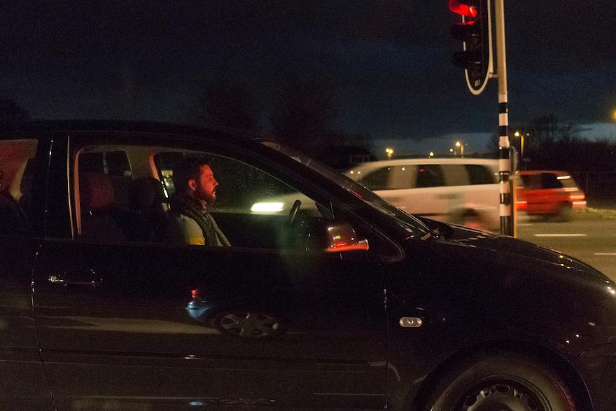 Nederland, Amersfoort, 7 jan 2014<br /> Man in auto wacht voor rood stoplicht in avondspits Amersfoort<br /> <br /> Foto: Michiel Wijnbergh