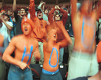 """Adam Ziemba, left, Brendan Bunkart, middle, and Alex Garrison explode with cheer with the word """"HOO"""" on their chests during the Wake Forest/ UVa basketball game in Charlottesville, VA"""