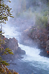 Water rushes through Firehole Canon in Yellowstone National Park creating a beautiful river and waterfall.