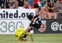 WASHINGTON, DC - AUGUST 4, 2012:  Dwayne DeRosario (7) of DC United is felled by Carlos Mendes (4) of the Columbus Crew during an MLS match at RFK Stadium in Washington DC on August 4. United won 1-0.