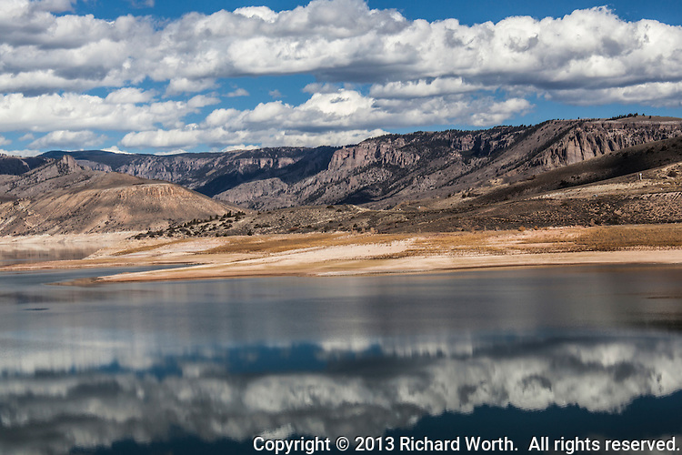 Clouds above and below frame the cliffs surround Blue Mesa Reservoir on the Gunnison River in southwestern Colorado.