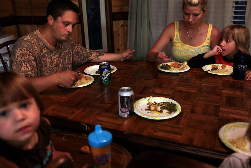 Kimmie Serigne with his wife Jami Serigne have fried shrimp for dinner with their sons Joseph Serigne, 1, left, and Morgan Serigne, 6, right, in their home on the outskirts of Chalmette, LA on May 21st, 2010. The shrimp was caught in the local bayou to be used for bait after the shrimping industry was shut down after the BP oil spill in the Gulf of Mexico.