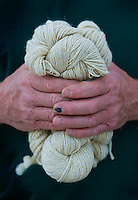A farmer holds yarn woven from the sheep raised on his farm. His finger nail is darkened from an accident.