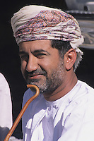 Sumail, Oman, Arabian Peninsula, Middle East - Omani Man, a government employee, wearing the traditional Omani turban, an msarr or massar, and a white robe, or dishdasha.  He is resting his chin on a traditional walking stick, an asa, or khuzran.