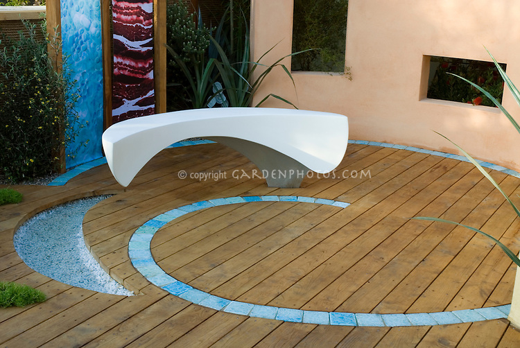 Modern design garden bench on circular wood patio, inset with curving blue designs, in a walled garden