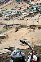 A Peruvian water distribution worker with a pipe fills a tank with drinking water on the dusty hillside of Pachacútec, a desert suburb of Lima, Peru, 22 January 2015. Although Latin America (as a whole) is blessed with an abundance of fresh water, having 20% of global water resources in the the Amazon Basin and the highest annual rainfall of any region in the world, an estimated 50-70 million Latin Americans (one-tenth of the continent's population) lack access to safe water and 100 million people have no access to any safe sanitation. Complicated geographical conditions (mainly on the Pacific coast), unregulated industrialization (causing environmental pollution) and massive urban poverty, combined with deep social inequality, have caused a severe water supply shortage in many Latin American regions.