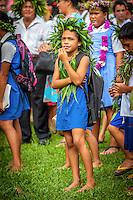 A young girl with ti leaf adornments witnesses the investiture of Makirau Haurua, Aitutaki Island, Cook Islands.