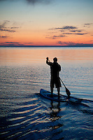 A single stand up paddleboard paddler silhouetted during an evening workout on Lake Superior at Grand Marais Michigan.