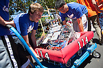 Nicholas Bousse and Mike Hua, left to right, lift their robot back onto the cart after competing in the first round of RoboNanza June 27.