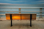 Bench along coastline at dusk.