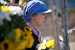 Naomi Hiratsuka, 37, whose daughter Koharu was swept away with 73 fellow elementary school students and teachers during the March 11 tsunami, arranges flowers at an ad hoc  shrine outside her daughter's school in Ishinomaki, Miyagi Prefecture, Japan on 07 Sept. 2011. Photograph: Robert Gilhooly