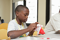 New York, NY, USA - June 23, 2012: A young folder concentrates on his work. Sipho Mabona teaches a class how to fold his original design, a complex origami bear. He helps young folders how to coordinate pre-creasing.
