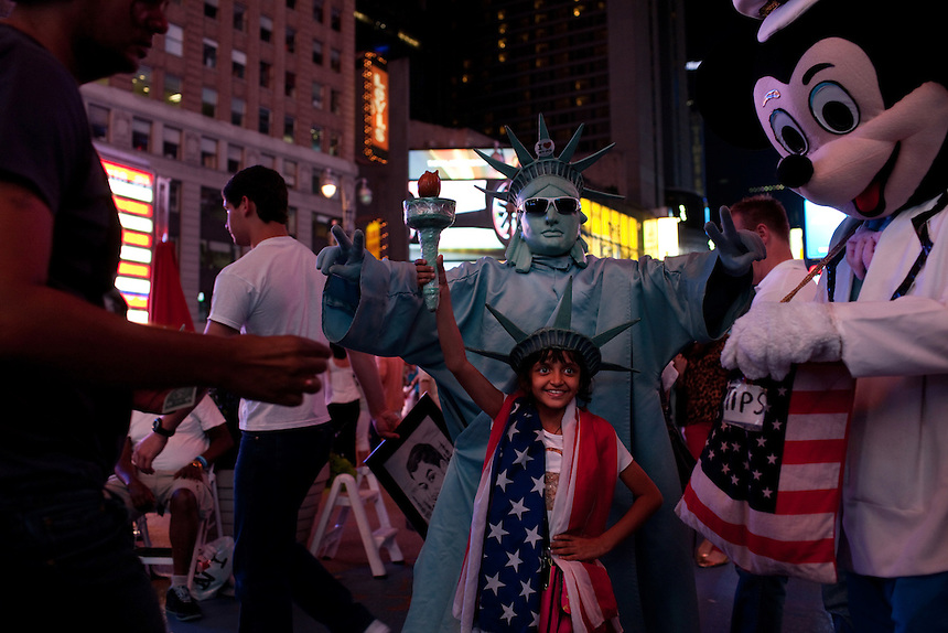 Tourists have their photograph taken in Times Square, New York, on June 23, 2012.