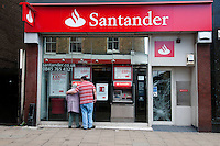 A man stands with an elderly woman outside a closed Santander Bank on Mare Street in the London borough of Hackney, with the door smashed. London saw the beginnings of riots on Saturday evening, after a peaceful protest in response to the shooting by police of Mark Duggan during an attempted arrest, escalated into violence. By the third night of violence, rioting had spread to many areas of the capital and to other cities around the country.
