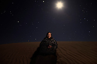 Fatimetu Hamed Mohamed, 22. Pictured in sand dunes near Smara refugee camp, Algeria: 'I'm a refugee and I want to go back home. I like it here but I would prefer to live in the Smara in the occupied territory. I swear to God it's difficult to live here, everything is difficult, the conditions, no good life, no jobs, not enough food. The best thing is that we are all together here. I would love to do a sports job. I run the Sahara marathon, I did it four times.'.