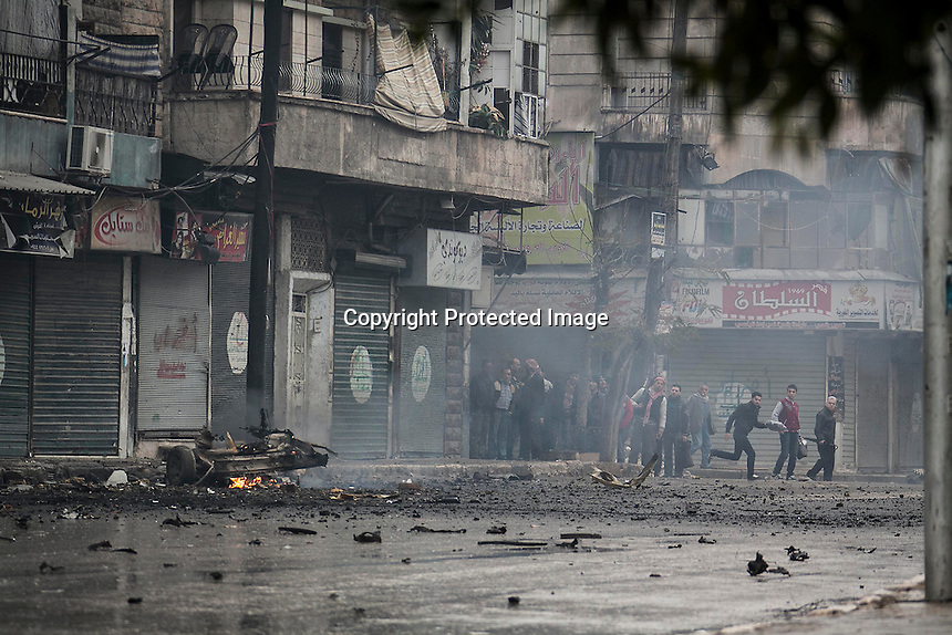 In this Monday, Dec. 17, 2012 photo, Syrian residents take cover as smoke rises from a car in fire after a mortar shell landed on a commercial street killing two people in the Bustan Al-Qasr district of Aleppo, Syria. (AP Photo/Narciso Contreras)